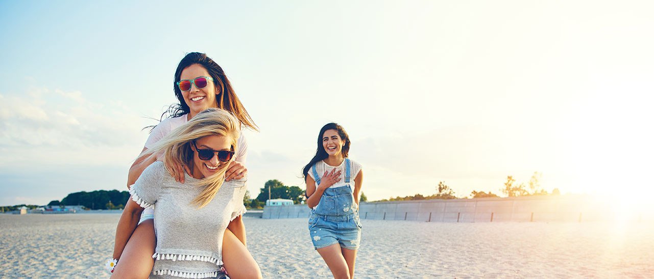 group of young women laughing on a beach